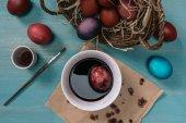 pohled shora Cup s barvou a velikonoční vajíčko na stole