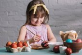 Fotografie adorable kid painting easter eggs with brush