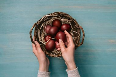 cropped image of woman putting easter eggs in basket