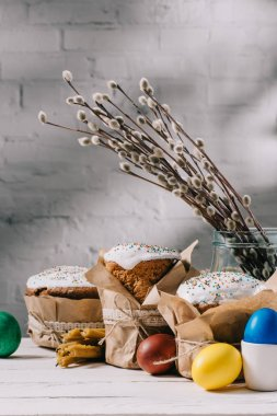 easter bread, painted eggs, catkins and candles on wooden table