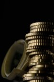 Photo selective focus of stack of coins and rolled banknotes isolated on black