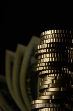 selective focus of stack of coins and banknotes isolated on black