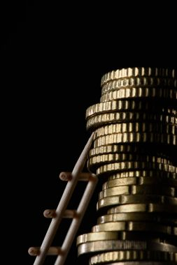 close up view of pile of coins with little wooden ladder isolated on black
