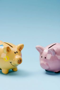 close up view of two yellow and pink piggy banks isolated on blue