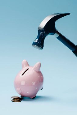 close up view of pink piggy bank with stack of coins and hammer isolated on blue