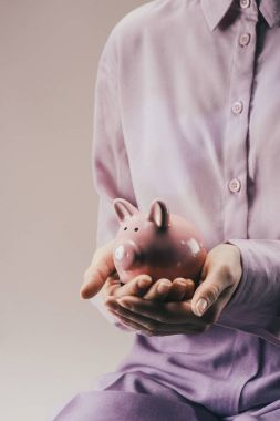 partial view of woman holding pink piggy bank in hands isolated on lilac