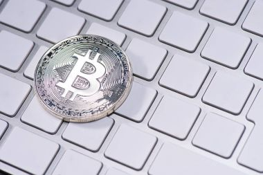 Close up view of silver bitcoin on white keyboard stock vector
