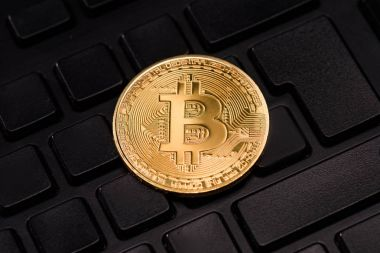 Close up view of golden bitcoin in black keyboard stock vector