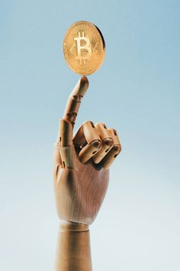 Close up view of wooden puppet hand holding golden bitcoin isolated on blue