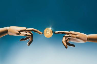 Close up view of wooden puppet hands and golden bitcoin on blue backdrop