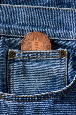 Close up view of bronze bitcoin in denim pocket