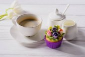 close up view of tulips, cup of coffee, sweet muffin and jag of cream on white wooden tabletop