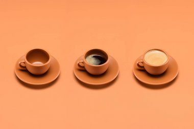 close up view of arrangement of empty cup and two cups of coffee isolated on peach
