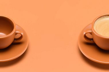 Close up view of empty cup and cup of coffee isolated on peach stock vector