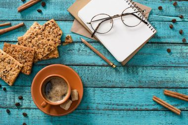 flat lay with cup of coffee, cookies, eyeglasses, empty notebook, roasted coffee beans and cinnamon sticks around on blue wooden tabletop