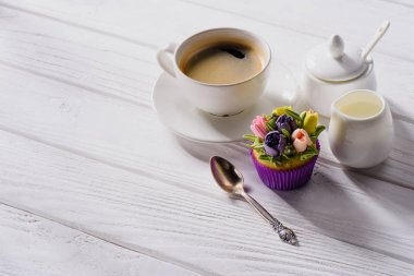 close up view of cup of coffee, sweet muffin, spoon and jag of cream on white wooden tabletop