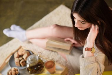 selective focus of woman with book and cup of tea on wooden tray at home