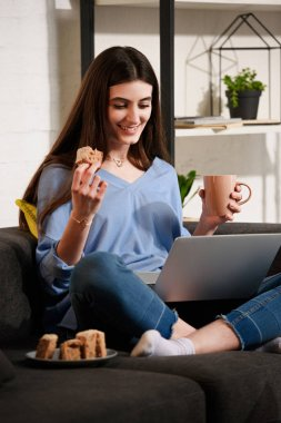 smiling woman with cup of coffee and piece of cake using laptop on sofa at home