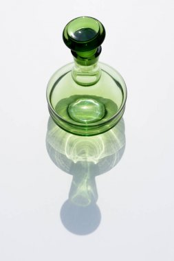 close up view of empty glass bottle and cork on white backdrop