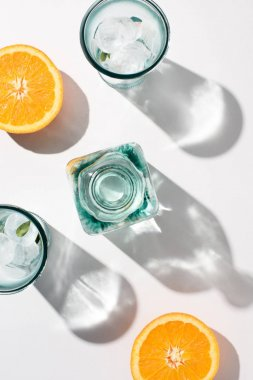 top view of pieces of orange, bottle and glasses with ice on white surface