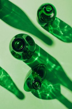top view of arranged empty green glass bottles with shadows on tabletop