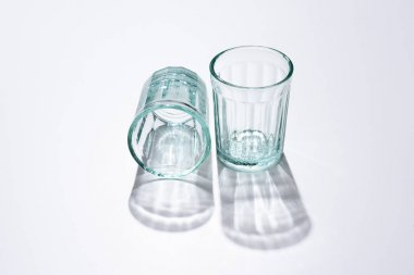 Close up view of empty glasses and shadows on white surface stock vector