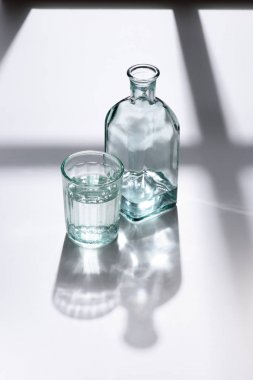 close up view of glass and bottle with water on white surface
