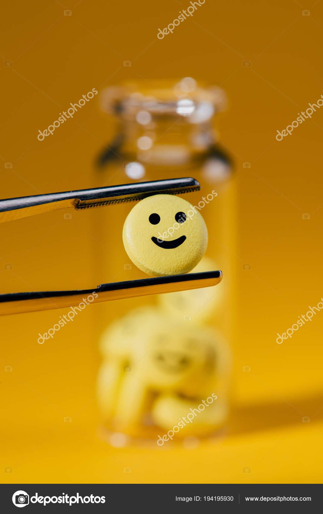 close shot pill smiley face tweezers glass bottle yellow stock