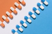 Fotografie top view of blue and orange pills on colorful surface