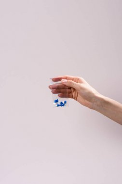 cropped shot of woman holding zip bag with pills isolated on grey