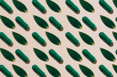 top view of phytotherapy pills with green leaves in rows pattern on beige surface
