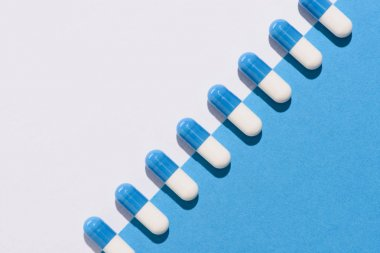 top view of row of pills on halved white and blue surface
