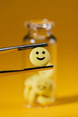 close-up shot of pill with smiley face in tweezers and glass bottle on yellow
