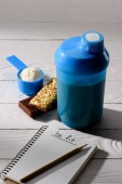 Photo protein shaker with energy bars and measuring tape on white wooden table