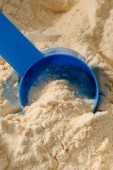 Photo close-up shot of plastic spoon dipping in pile of protein powder