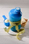 Photo close-up shot of protein shaker tied with measuring tape and energy bars on white wooden table