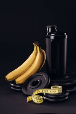 black protein shaker on pile of weight plates with bananas and measuring tape isolated on black