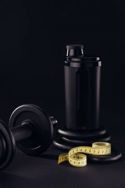 protein shaker with dumbbell and measuring tape isolated on black