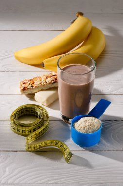 glass of protein shake with bananas and energy bars on white wooden table