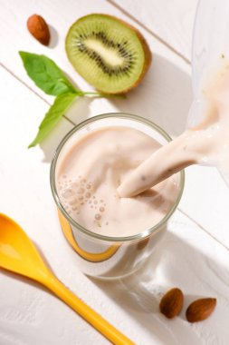 high angle view of protein drink pouring into glass on white wooden table with half of kiwi