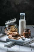 Photo delicious cookies dipped in hot chocolate and sesame with bottle of milk