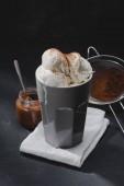 Fotografie lahodnou zmrzlinu v poháru a síto na stole
