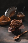 Photo yummy chocolate cupcake with icing, cocoa powder and sieve on table