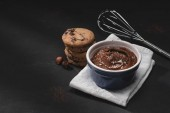 Photo bowl with chocolate dessert, whisk and cookies on tabletop