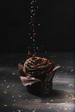 tasty chocolate cupcake with glaze and sugar spreading on table