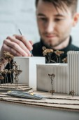 selective focus of architect coloring self made building miniature with paintbrush in office