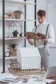 Selektivní fokus architekta čtení časopisů a model budovy na pracovišti v úřadu