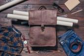 plochý ležela s mužské košile, džíny, hodinky a plány v batohu na dřevěnou desku