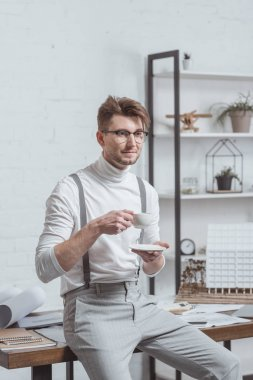 portrait of architect in eyeglasses with cup of coffee at workplace in office