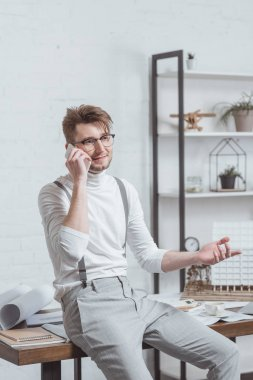 portrait of architect in eyeglasses talking on smartphone at workplace in office